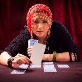 無地のカードをコチラに見せる女性占い師