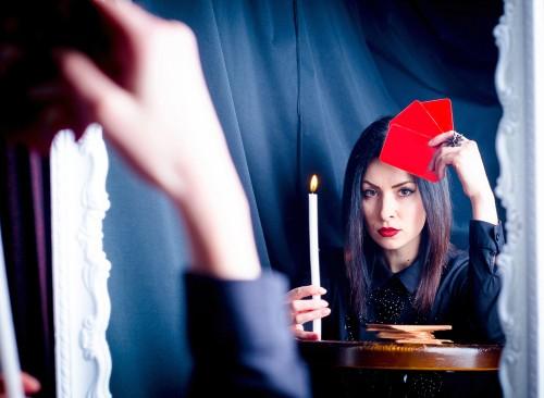 ろうそくとカードを手にしながら鏡を見る女性
