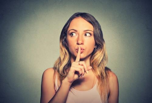 右手の人差し指を自分の口にあてる女性